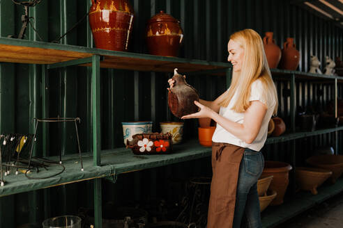 Smiling woman with blond hair holding pottery while standing by shelf in workshop - MRRF00216