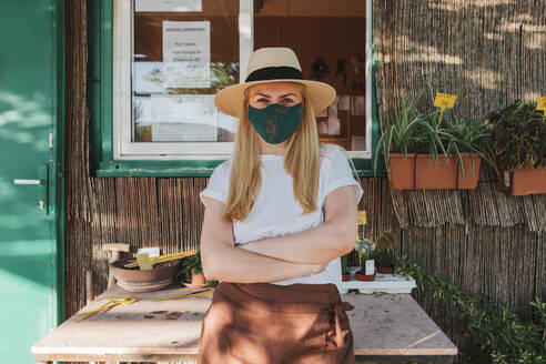 Female owner wearing hat and mask with arms crossed standing by table outside plant nursery - MRRF00246