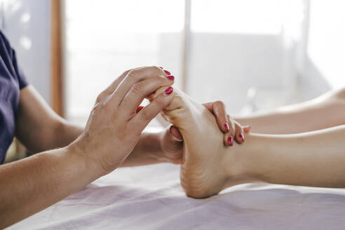 Close-up of therapist giving foot massage to female customer on table in health spa - EBBF00539