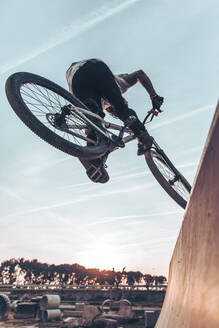 Carefree young man performing stunt with bicycle on ramp against sky in park during sunset - ACPF00789
