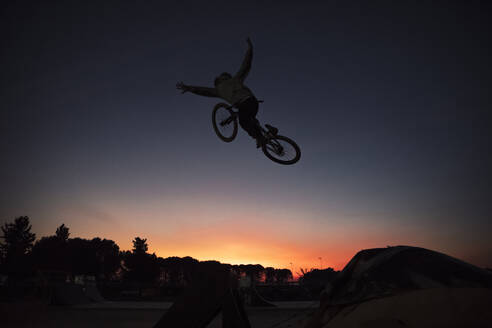 Carefree silhouette man performing stunt with bicycle against clear sky during sunset - ACPF00798