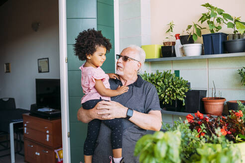 Grandfather wearing sunglasses carrying granddaughter in balcony - MEUF01902