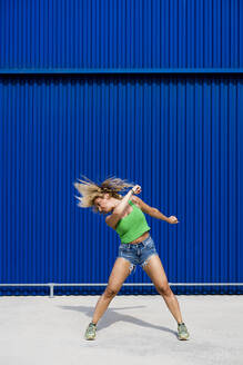 Young woman dancing in front of blue wall in the city - MAUF03504