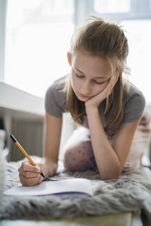 Girl learning at home, writing in exercise book - DKOF00004