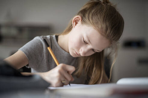Girl learning at home, writing in exercise book - DKOF00007