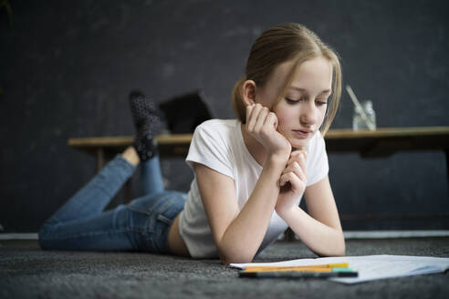 Girl lying on carpet and learning at home - DKOF00028