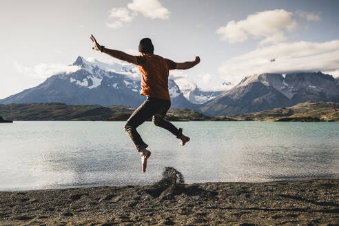 Man with arms outstretched jumping at Lake Pehoe in Torres Del Paine National Park Patagonia, South America - UUF20847