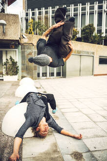 Male friends jumping upside down in city - EHF00738