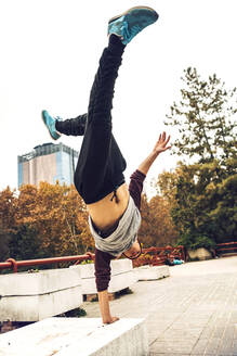 Young man doing handstand against clear sky - EHF00744