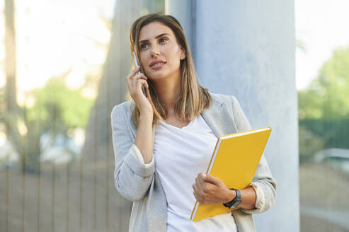 Businesswoman looking away while talking on mobile phone - KIJF03201