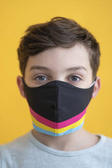 Close-up of boy wearing multi colored mask against yellow background - SNF00483