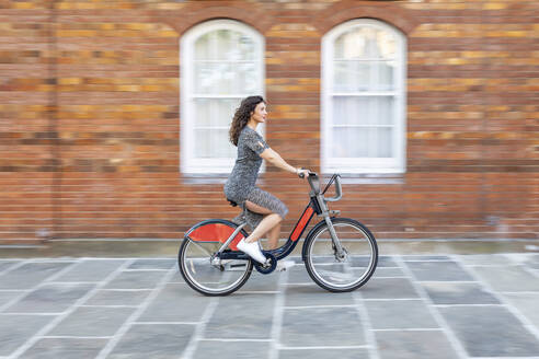 Blurred motion of young woman riding bicycle on street by building in city - WPEF03230