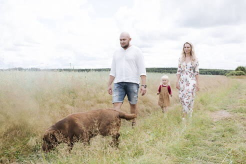 Russia, Ryazan, happy family with chocolate labrador retriever dog walking by country road across the oat field - EYAF01257