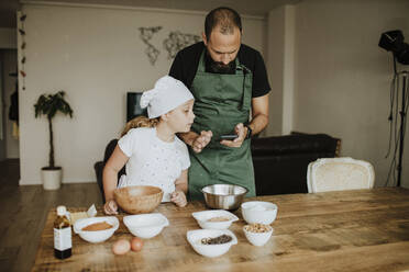 Father and daughter baking cookies and using smartphone at home - GMLF00419