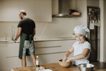 Father and daughter baking cookies at home - GMLF00422