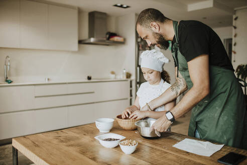 Father and daughter baking cookies at home - GMLF00425