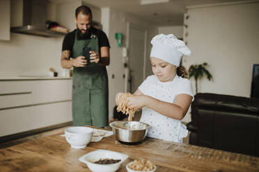 Father and daughter baking cookies at home, father taking a picture with smartphone - GMLF00428