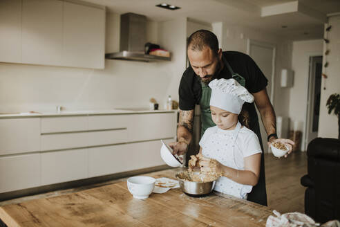 Father and daughter baking cookies at home - GMLF00431