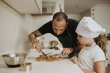 Father and daughter baking cookies at home - GMLF00434