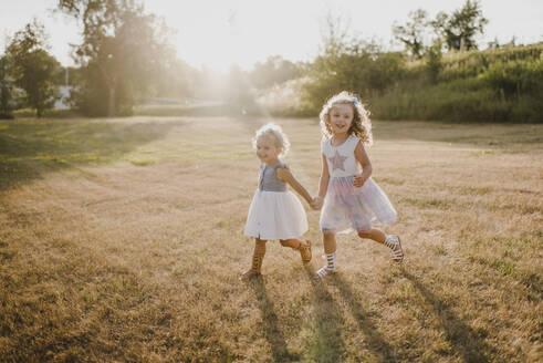 Happy girls on a meadow in backlight - SMSF00087