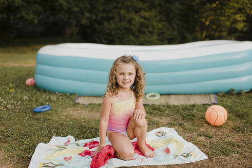 Portrait of a smiling girl on towel at inflatable swimming pool in garden - SMSF00111