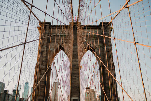Perspective view of beautiful bridge gates with cables on background of New York city - ADSF09533