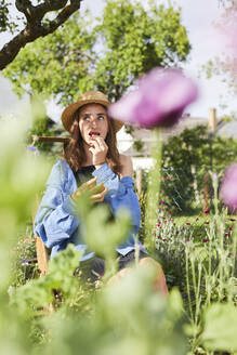Young woman wearing hat eating strawberry while sitting in vegetable garden - UKOF00046