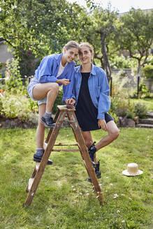 Smiling female friends standing on ladder in community garden - UKOF00064