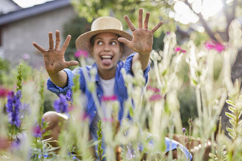 Cheerful young woman showing dirty hands while sitting amidst plants in garden - UKOF00067