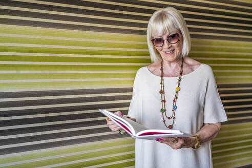 Stylish senior woman wearing sunglasses reading book while standing against wall at home - DLTSF01049