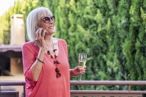 Senior woman holding champagne flute talking over mobile phone while standing in balcony - DLTSF01058