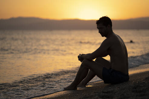 Shirtless thoughtful mid adult man sitting at shore against sky during sunset - MPPF01012