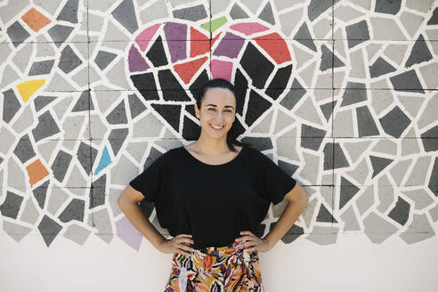 Portrait of smiling woman in front of colorful wall - XLGF00434