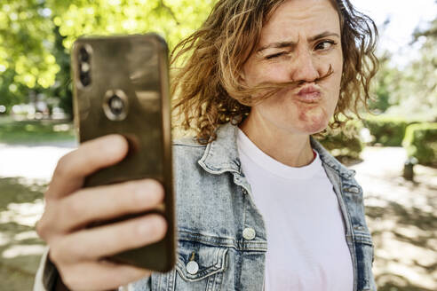 Mid adult woman making face while taking selfie with mobile phone in park - JATF01235