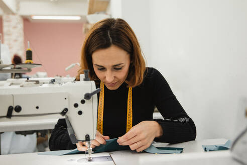 Adult woman sitting at table and making garment part on sewing machine while working in professional studio - ADSF10028