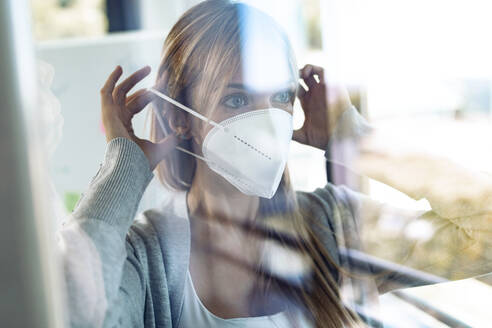 Portrait of young woman putting on protective mask behind window pane - JSRF00981