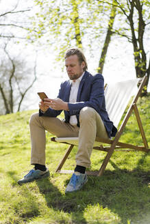 Mature businessman text messaging through mobile phone while sitting on chair at park - JOSEF01443