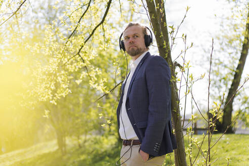 Male entrepreneur listening music while looking away at park on sunny day - JOSEF01476