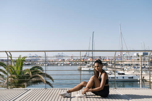 Valencia, Spain. Sporty woman sitting on the floor, with the port in the background, on a sunny day. - EGAF00639
