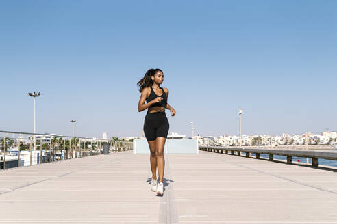 Woman jogging at harbor against clear sky during sunny day - EGAF00642