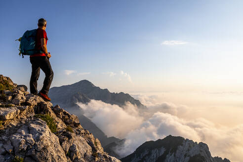 Man admiring view while standing on mountain peak at Bergamasque Alps, Italy - MCVF00555