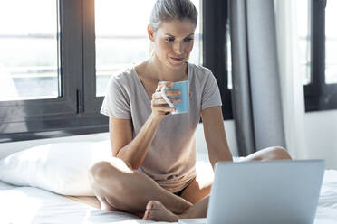 Blond woman sitting on bed, using laptop and drinking coffee - JSRF00985