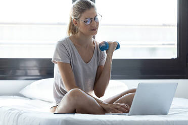 Blond woman using laptop during training with dumbbell sitting on bed - JSRF00991