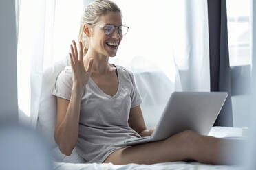 Blond woman using laptop and waving during video call - JSRF00994
