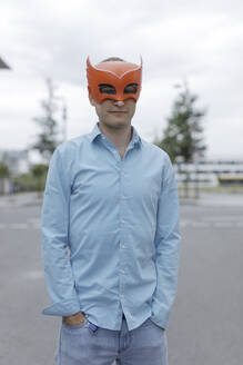Man wearing mask with hands in pockets in city - KMKF01451