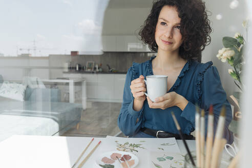 Pensive brunette woman artist sitting at table with cup of coffee and looking away in workplace - ADSF10526