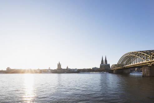 Germany, North Rhine-Westphalia, Cologne, Sun setting over Rhine with Hohenzollern Bridge and Cologne Cathedral in background - GWF06708
