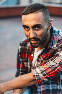 Confident young man wearing plaid shirt at rooftop in city - EHF00787
