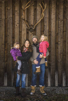 Portrait of a smiling family in front of a cabin with deer antlers - DHEF00203