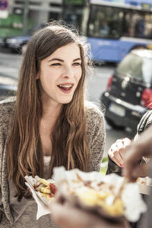 Portrait of a teenage girl hanging out with friends in the city having a snack - DHEF00236